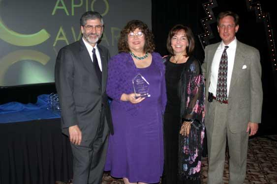 Longtime CAPIO members Judy Rambeau, Scott Summerfield and Tom Manheim, all past Clark Award winners, presented a plaque of achievement to Ann Erdman (with plaque) during the 2004 Conference and Awards Ceremony in Monterey.