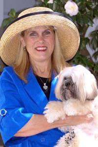 Award winner, Linda Crabill Byrne, posing in a hat with her Llasa Apso dog.