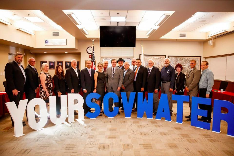"Group of people dressed formally in a board room in front of cut out letters that reads ""Your SCV Water"""